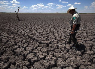 In this Associated Press photo, a Texas State Park police officer walks across a cracked lakebed in August 2011. The lake once spanned more than 5,400 acres.