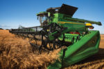 John Deere X Series harvesting wheat